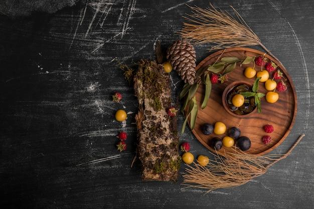 Mistura de frutas vermelhas em uma travessa de madeira com galhos de carvalho e cones de lado no meio