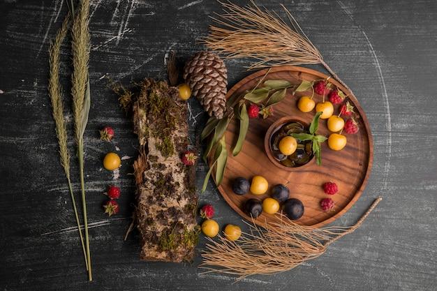 Mistura de frutas vermelhas em uma travessa de madeira com ramos de carvalho e cones de lado