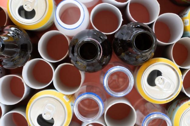 Mistura de garrafas de vidro, papelão, plástico e latas, conceito de reciclagem, foco selecionado