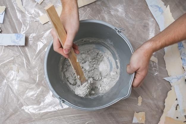 Mistura de gesso branco em um balde com um agitador. fechar-se.