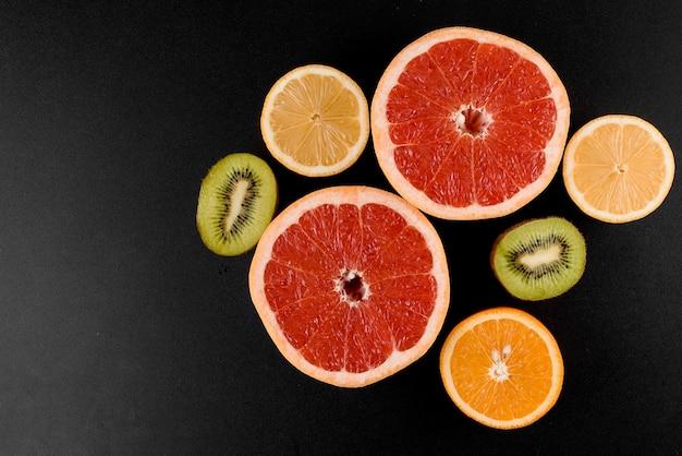 Mistura de laranja, kiwi, toranja na superfície preta