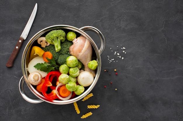 Mistura de legumes e coxa de frango na panela com espaço de cópia