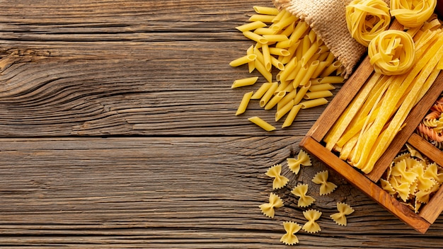 Mistura de macarrão cru em caixa de madeira na mesa