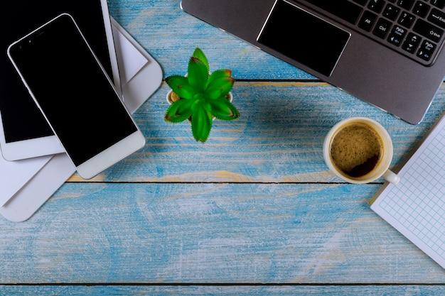 Mistura de material de escritório com aparelhos de telefone inteligente trabalhando em um computador laptop em uma xícara de café em um fone de ouvido sem fio