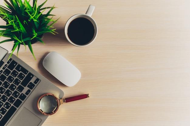 Mistura de material de escritório e gadgets em um fundo de mesa de madeira.