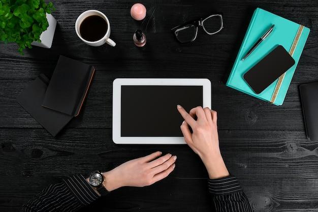 Mistura de material de escritório e gadgets em uma mesa de madeira vista de fundo