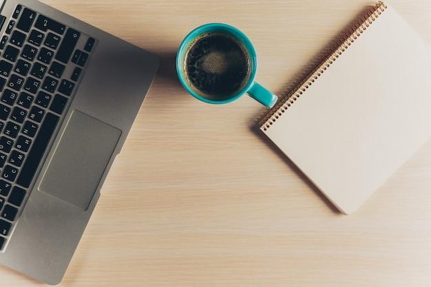 Mistura de material de escritório e gadgets em uma mesa de madeira.