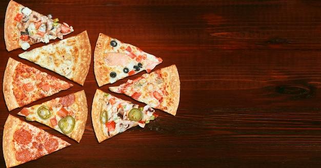 Mistura de oito pizzas diferentes em um menu de mesa de madeira, conceito de escolha e diversidade