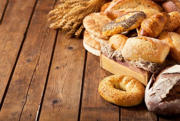 Mistura de pão fresco com espigas de trigo na mesa de madeira