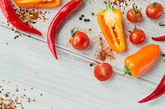 Mistura de pimentão fresco colorido, tomate cereja e especiarias na mesa de madeira branca simulada