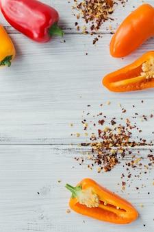 Mistura de pimentas frescas coloridas e especiarias de sementes secas na mesa de madeira branca