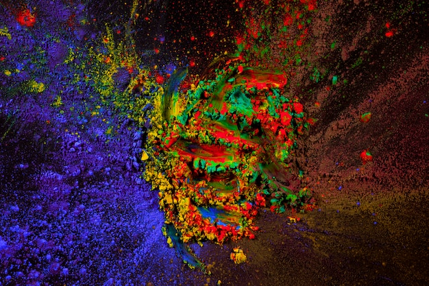 Mistura de pó de cor holi espalhar sobre fundo escuro