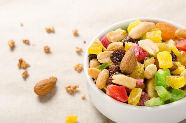 Mistura de porcas e frutas secas - amêndoas, amendoins, passas no fundo branco em uma tigela.