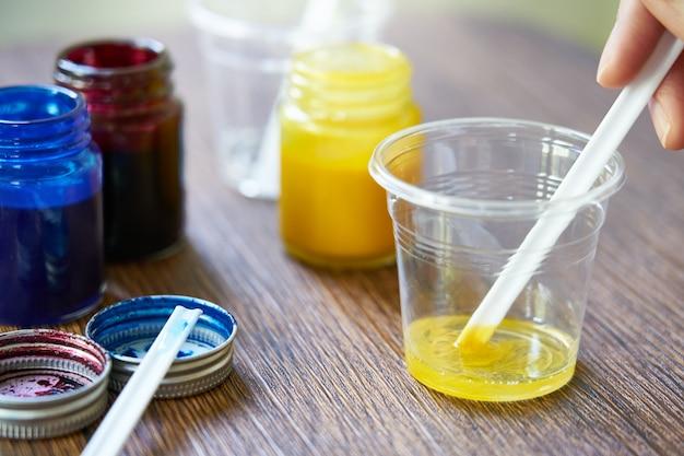 Mistura de produtos químicos de resina amarela em copo de plástico, processo de fabricação de acessórios a partir de resina