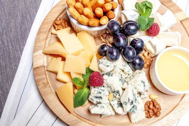 Mistura de queijos com molho de mel, pão e uva no palato wooren
