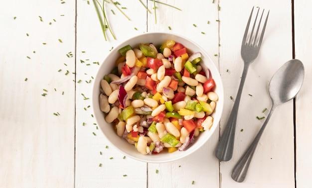 Mistura de salada de feijão e talheres
