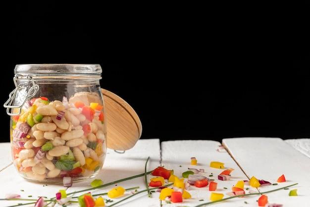 Mistura de salada de feijão em uma jarra com fundo preto vista frontal