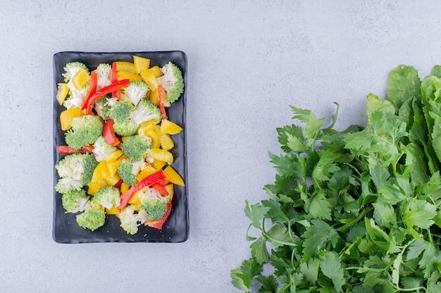 Mistura de salada dietética em uma travessa preta ao lado do molho de salsa no fundo de mármore. foto de alta qualidade