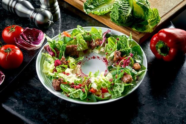 Mistura de salada quente com fígado de frango e romã servido em um prato branco sobre uma mesa de mármore escuro. comida do restaurante.