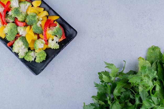 Mistura de salada saudável em uma travessa preta ao lado do molho de salsa no fundo de mármore. foto de alta qualidade