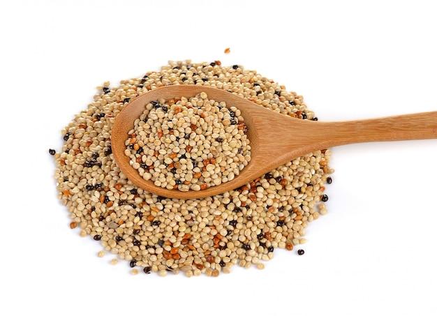 Mistura de sementes na colher de madeira na parede branca. ração para pássaros