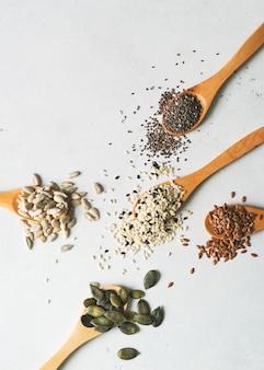 Mistura de sementes no fim da colher acima no fundo branco. vegan e conceito de comida vegetariana