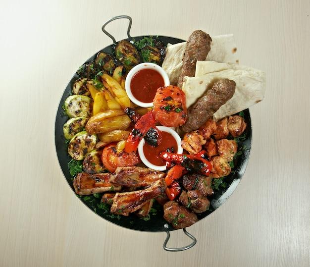 Mistura de shish kebab. vários tipos no tapete torrado com vegetais closeup