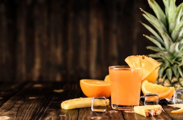 Mistura de suco de laranja e abacaxi em fundo de madeira