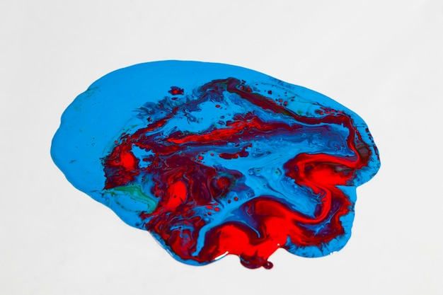 Mistura de tinta azul e vermelha de alto ângulo sobre fundo branco