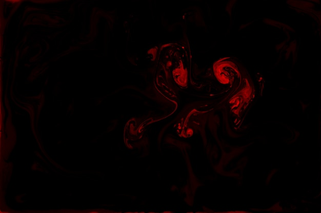 Mistura de tintas acrílicas vermelhas sobre fundo preto