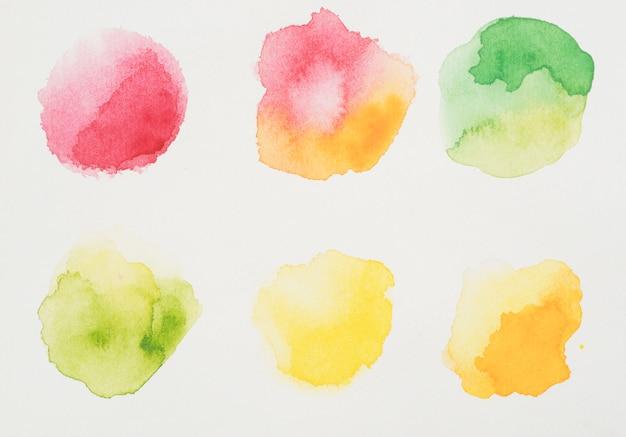 Mistura de tintas vermelhas, amarelas e verdes em papel branco