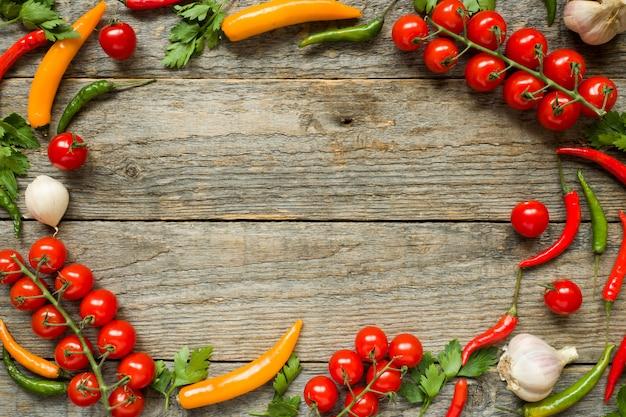 Mistura de tomate cereja pimenta em um ramo de alho e outras especiarias em um fundo de madeira cópia espaço
