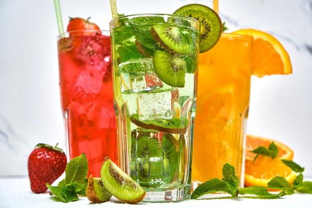 Mistura de três deliciosas garrafas de limonada gelada de kiwi e laranja e morango com hortelã e pedaços de frutas em superfície clara