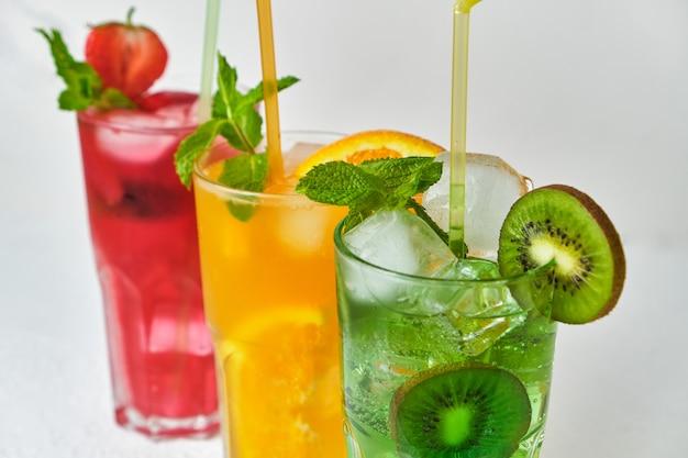 Mistura de três deliciosas garrafas de limonada gelada de kiwi, laranja e morango com hortelã na superfície clara