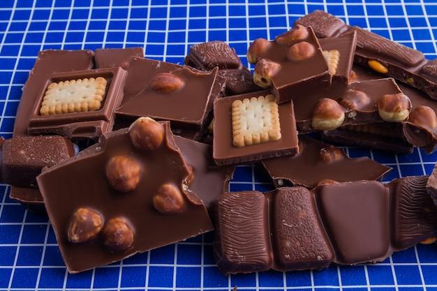 Mistura de vários chocolates rachados sobre fundo xadrez azul. pilha de diversos pedaços de barra de chocolate escuro.