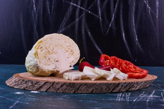 Mistura de vegetais em uma travessa de madeira com pimenta e repolho no espaço azul.