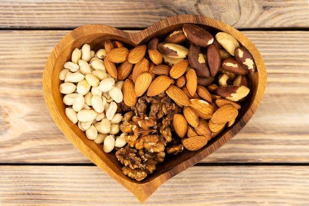 Mistura nutricional natural de várias nozes em uma placa de madeira em forma de um símbolo de coração em uma mesa de madeira marrom