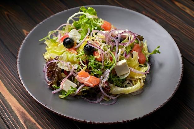 Mistura para salada com salmão, queijo feta, cebola e azeitonas, em um prato, sobre uma superfície de madeira