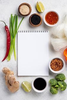 Mistura plana leiga de ingredientes alimentares asiáticos com caderno em branco