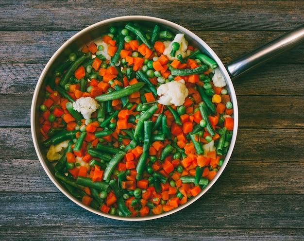 Mistura vegetal de cenouras, ervilhas, feijão verde e couve-flor em uma frigideira em uma velha mesa de madeira