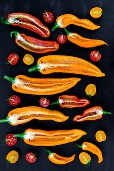 Misturado da meia pimenta vermelha e amarela com um ramo verde perto do tomate de cereja em um backround preto.