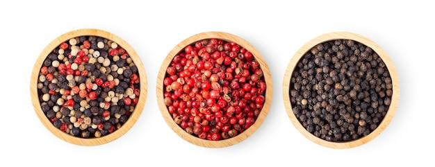 Misturado de pimentas quentes, vermelhas, pretas, brancas em uma tigela de madeira, isolado no fundo branco. vista do topo