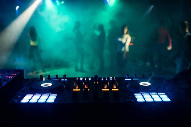 Misturador de música no estande do dj na boate com as pessoas na pista de dança e atmosfera de noite