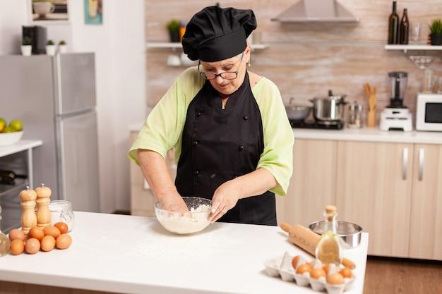 Misturar farinha com ovos para fazer massa para uma saborosa massa seguindo a receita tradicional. chef idoso aposentado com uniforme polvilhando, peneirando ingredientes crus e misturando.