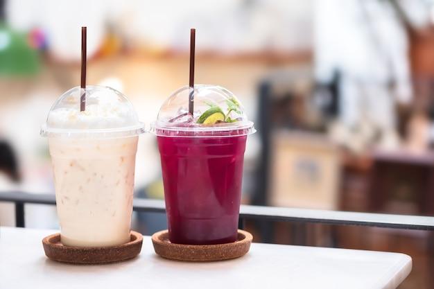 Misture a bebida gelada com mel gelado com chá de leite e flores de ervilha borboleta em um copo no fundo desfocado