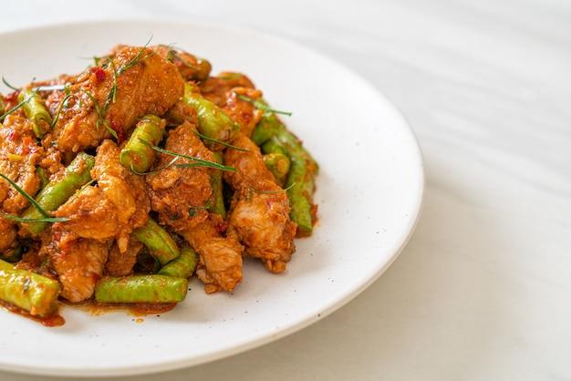 Misture a carne de porco frita e a pasta de curry vermelha com feijão