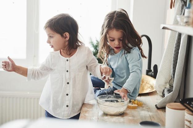 Misture a massa e segure instrumentos coloridos especiais. amigos da pré-escola aprendendo a cozinhar com farinha na cozinha branca.