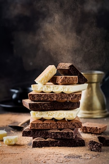 Misture a pilha de chocolate amargo, leitoso e branco poroso na superfície velha e escura. foco seletivo.