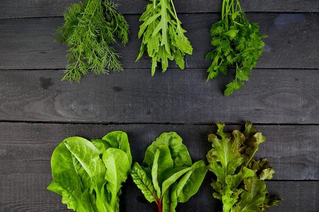 Misture a salada de folhas na mesa preta,