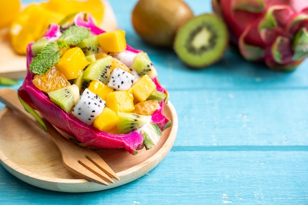 Misture a salada de frutas tropicais, servida ao meio uma fruta do dragão na mesa de madeira